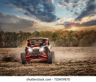 Racing quad bike with two pilots in helmets on the field. Sunset landscape. The concept of speed and freedom.