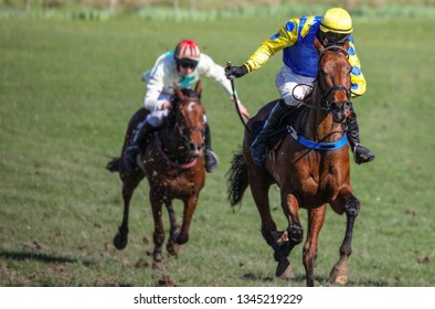 Racing towards the finish line, two race horses and jockeys competing for first place