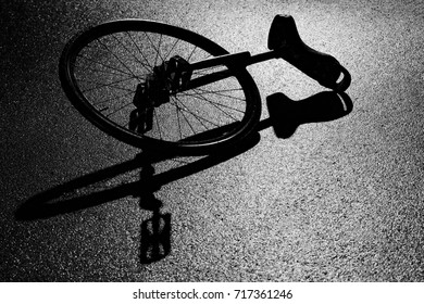 racing unicycle lying on the wet asphalt and casts bizarre shadows in the light of a lantern in the park in the evening