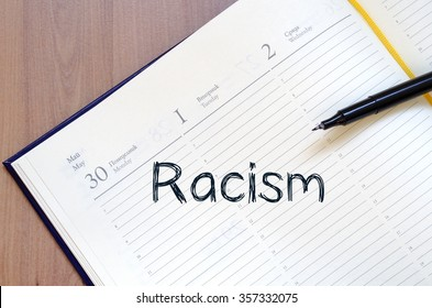 Racism text concept write on notebook with pen