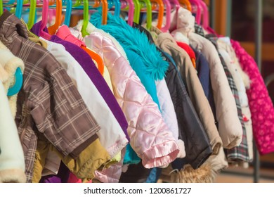 Rack of baby and children used dress, clothes displayed at outdoor hanger market for sale.