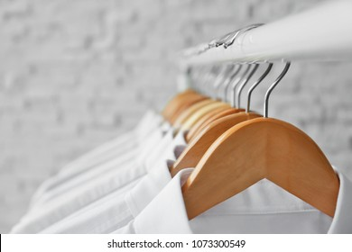 Rack with clean clothes on hangers after dry-cleaning, closeup