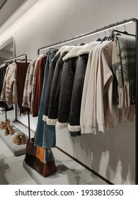 Rack with clothes on hangers and shoes in the store against the background of a small wall