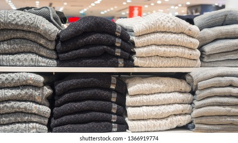 Rack of clothes in a store. Piles of warm sweaters different sizes, close up. Shopping, stock, trendy wear, hosiery and sale concept
