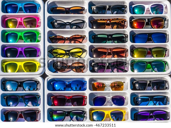 A rack of colorful generic sunglasses at an outdoor market.