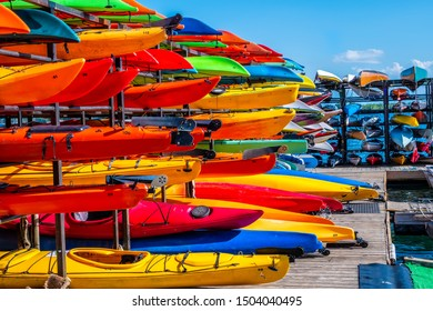 Rack of colorful kayaks and canoes.