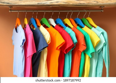 Rack with different child's clothes near coral wall, closeup