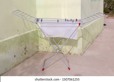 A rack dryer stands outside on a sunny day to dry white clothes. Foldable clothes dryer.