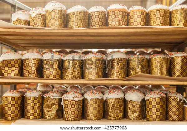 rack with easter cakes at the industrial bakery background texture