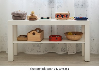 Rack with educational toys at home, Montessori area in an ordinary apartment. Scandinavian style interior and toys for children