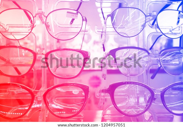 The rack with fashion eyeglasses in the optic store, decorated with red-blue gradient
