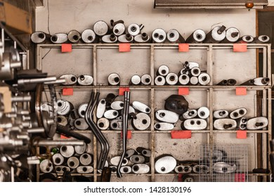 A rack full of exhaust pipes or silencers and other auto spare parts in a garage repair shop