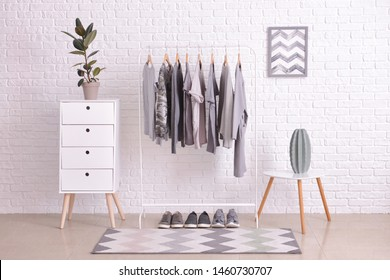 Rack with hanging clothes in interior of dressing room