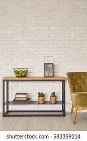 Rack with home decorations and stylish armchair