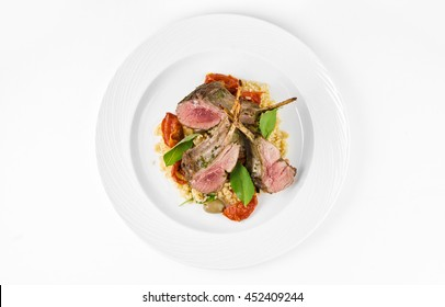 Rack of lamb with bulgur, dried tomatoes and lemon Moroccan on a plate on a white background, top view
