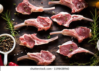 Rack of lamb , raw meat with bone on rustic kitchen table at wooden background