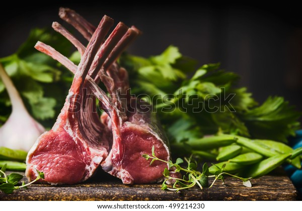 Rack of lamb , raw meat with bone on rustic kitchen table at wooden background, side view