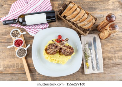 Rack of lamb , Lamb Ribs on rustic kitchen table at wooden background. Lamb ribs served on potato mash.Lamb chops with white wine on the table.