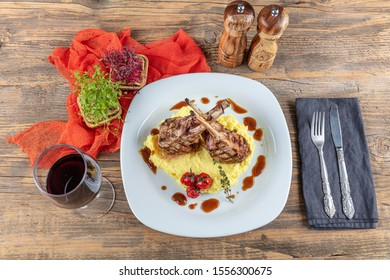 Rack of lamb , Lamb Ribs on rustic kitchen table at wooden background. Lamb ribs served on potato mash. Lamb chops with a glass of red wine.