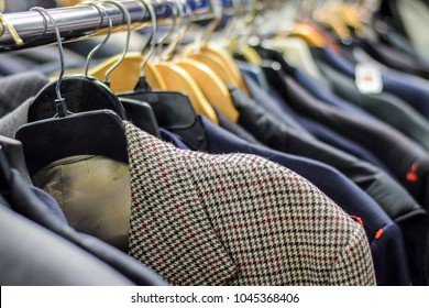 Rack of men's suit jackets hanging in boutique store