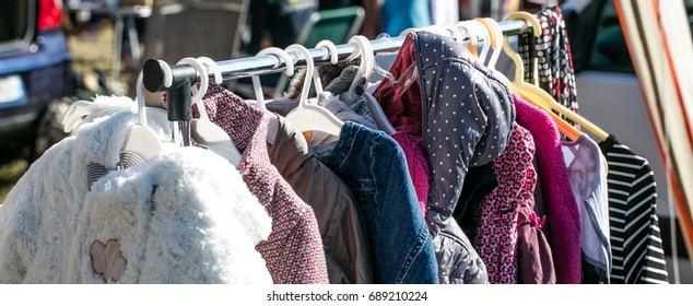 rack of second hand winter baby and children jackets and coats displayed at outdoor flea market for sale, exchange, recycle, donate and reuse against over-consumption shopping