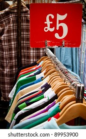 A rack of second-hand shirts and t-shirts at a market in London, all for a fiver: recession bargains.