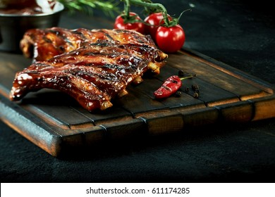 Rack of spicy barbecued chili spare ribs with a grilled cayenne pepper and tomatoes served on an old vintage wooden cutting board in a close up view