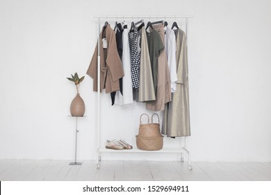A rack with stylish clothes next to a white wall in the room. Clothing retails concept. Advertise, sale, fashion.