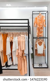 Rack with stylish clothes.Trendy color.In clothing store.Concept monochrome orange.Design.