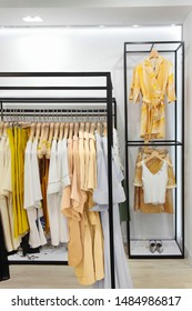 Rack with stylish clothes.Trendy color.In clothing store.Concept monochrome yellow .Design.