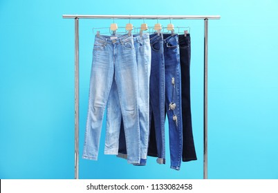 Rack with stylish jeans on color background
