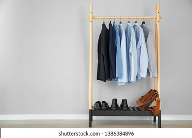 Rack with stylish male clothes near light wall