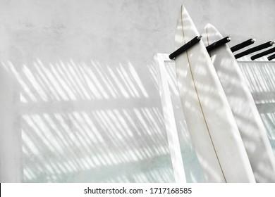 Rack mit zwei Surfbrettern auf grauem, betoniertem Hintergrund mit schönem Sonnenlicht. Aktiver Lebensstil, Sportausrüstung.  Miete Surfbrett in Bali.