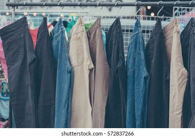 A rack of a variety of blue denim jeans in various shades of blue in market