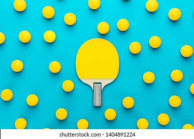 racket and many balls for table tennis on turquoise blue background. flat lay image of many table tennis balls with tennis paddle in the middle. minimalist photo of yellow ping-pong equipment
