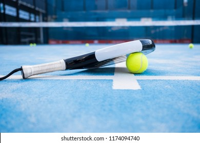 Racket and paddle tennis balls on the blue court.