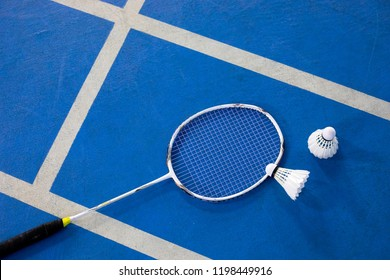 racket and shuttlecock in the blue badminton court floor