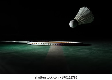racket and shuttlecock is floating before to the line.