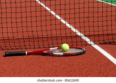 a racket and a tennis ball on a tennis court