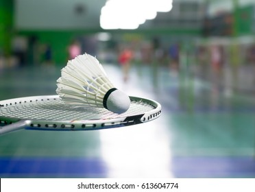 racket and white shuttlecock over blurred of badminton court with players playing badminton