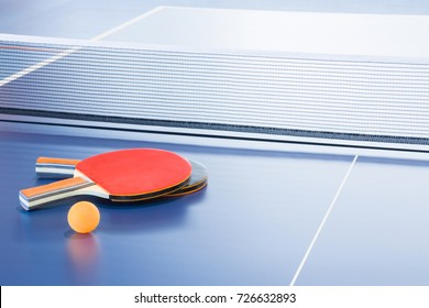 Rackets and ball on the blue tennis table. Indoor sport activity. Sport concept.