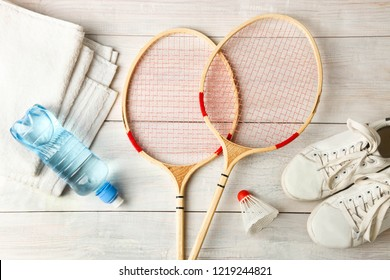 Rackets, shuttlecock and sport shoes on wooden background. Concept badminton.