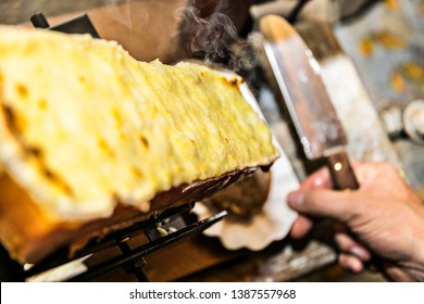 Raclette on the raclette grill is already grilled and spread with a knife on the bread and it smokes nicely