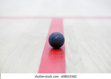 Racquetball equipment. Squash ball on the court on the red line. Photo with selective focus