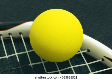 Racquetball on racket strings. Yellow frontenis ball laying on racket strings, over black background.