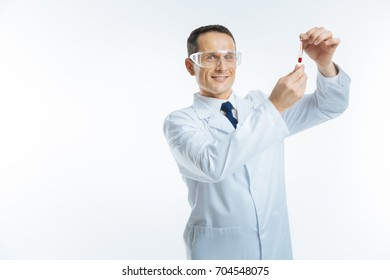 Radiant doctor looking at glass tube with blood sample