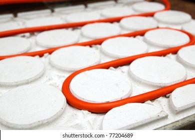 radiant floor heating tube red pipe curved in white circle pattern