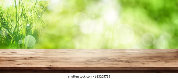 Radiant green spring background panorama with grass in front of a wooden table for a concept