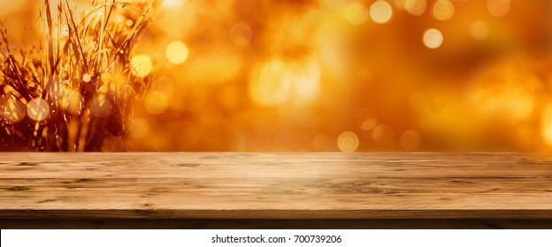Radiant orange golden autumn background with an empty rustic wooden table for a concept decoration