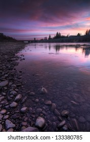 Radiant violet sunrise on the river shore with rocks